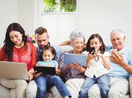 Happy family using technologies while sitting on sofa at home